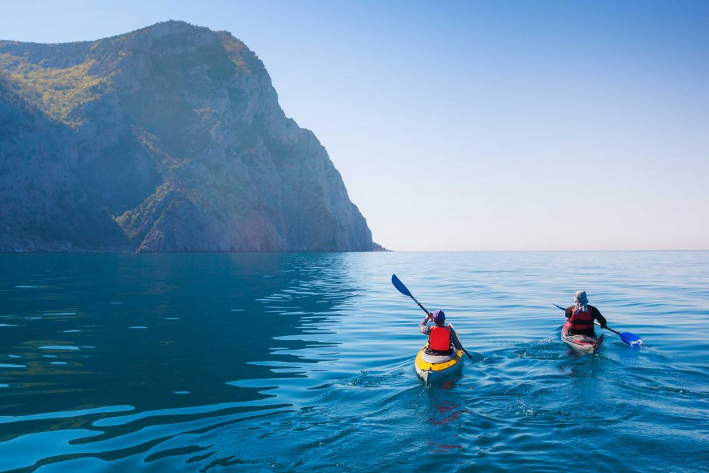 People in canoes at sea trying new things as a way to create new experiences
