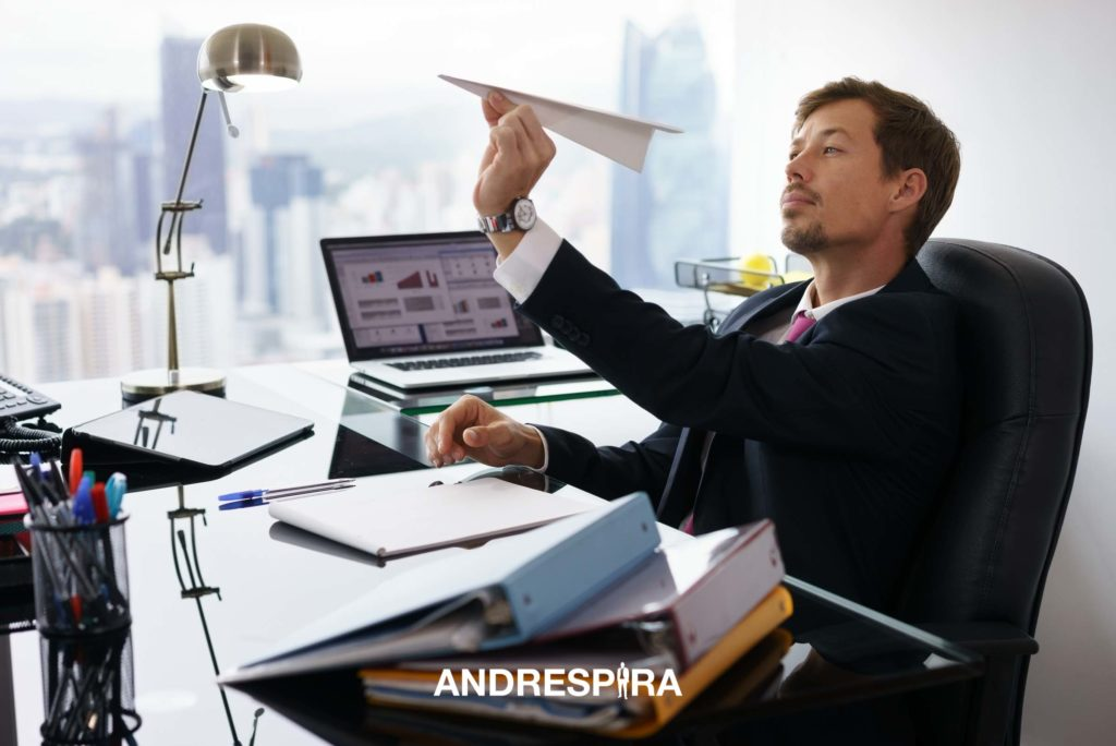 Man Playing with a Paper Plane at Work