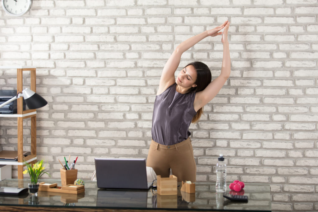 A Woman Stretching at Her Desk
