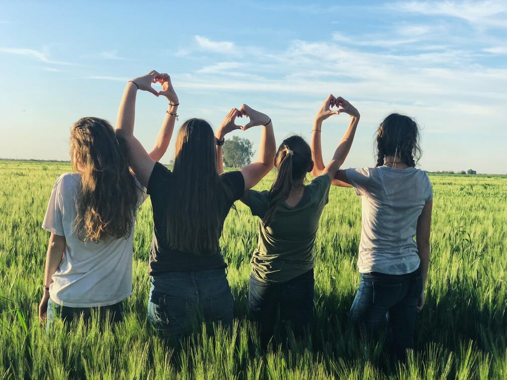 Four women forming hearts with their hands in a field