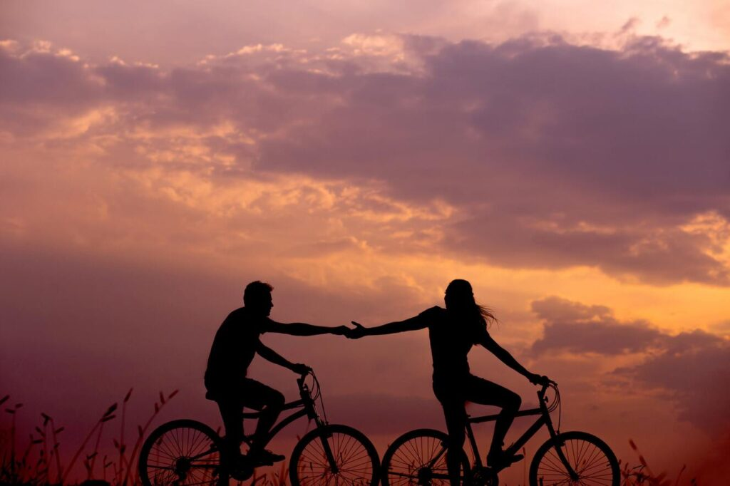 Women on Bike, holding hands with man during sunset