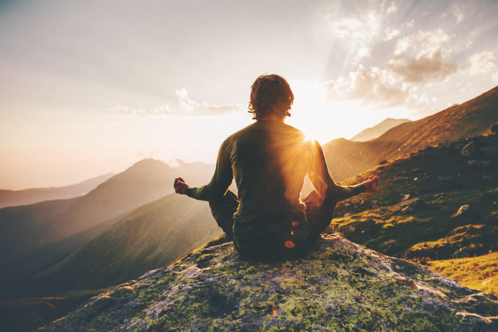 Man meditating on top of a mountain.