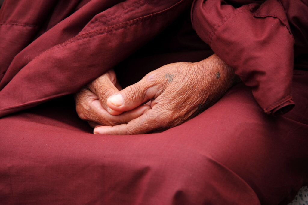 Ancient and aged Buddhist monks hands in red cloths