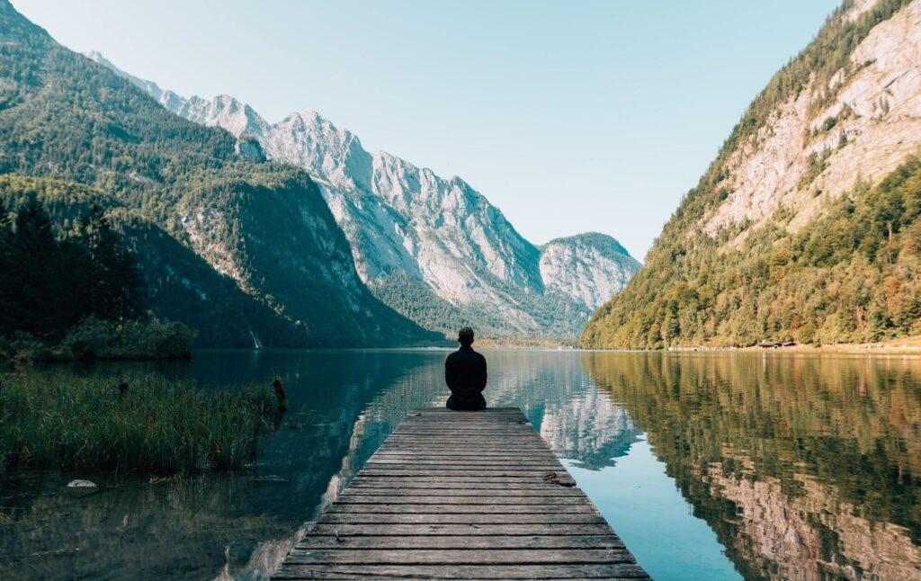 Man sitting on gray dock watching the view of river and mountains.
