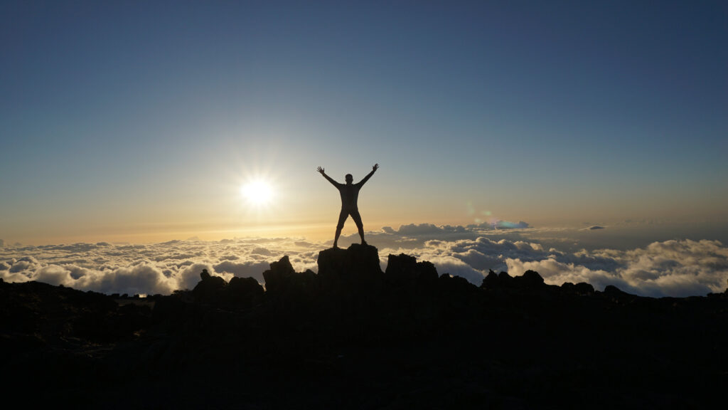 Man standing at the summit of a mountain cheering.
